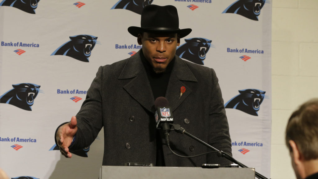 Carolina Panthers quarterback Cam Newton wears a black coat and hat as he talks with reporters during a post-game news conference after an NFL football game, Sunday, Dec. 4, 2016, in Seattle. The Seahawks won 40-7. (AP Photo/Stephen Brashear)