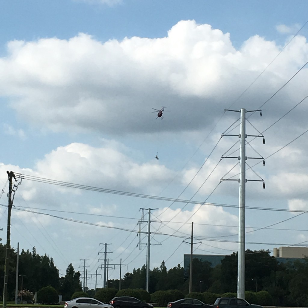 man dangles from helicopter